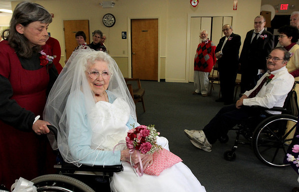 "ALLEGRA BOVERMAN/Staff photo. Gloucester Daily Times. Gloucester: ""Bride"" Alyce Brayman, 97, is wheeled down the aisle by ""Mother-of-the-Bride"" Kathy McCullough, during a Mock Wedding held at Day by Day on Tuesday morning. At far right is ""Groom"" Bill Grandmont, seated, ""mother-of-the-groom"" Jacqui Maley, and behind them, groomsmen (in back, from left: Jake Lattime, Ron Pool, Art Kippen and Joe Castellucci."