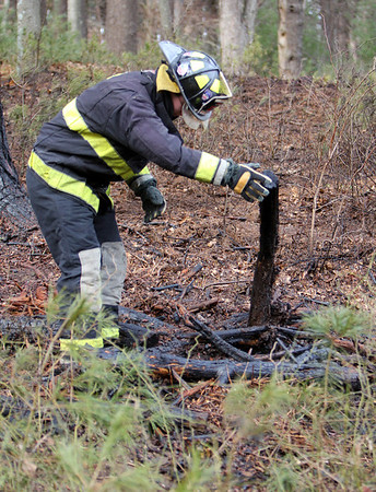 ALLEGRA BOVERMAN/Staff photo. Essex: Essex firefighters put out three separate brush fires that grew from controlled burns at 32 Haskell Court in Essex on Tuesday. FIrefighter Edward Neal overturns logs from one of the piles to make sure every surface gets saturated with water.