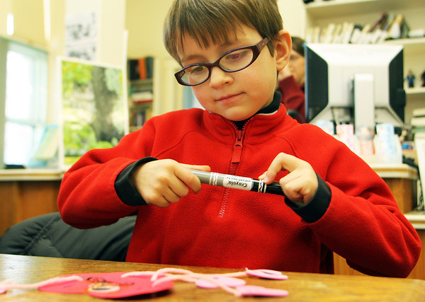 Jonah Stevens, 6, of Essex, snaps the cap to his marker and looks satisfyingly upon his Valentine's Day creation at the T.O.P.H. Burnham Library in Essex on Monday afternoon. Jesse Poole/Gloucester Daily Times Feb. 13, 2012