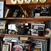 Photo Courtesy of Jake Levin/Gloucester Daily Times. Details of Roger Wonson's collection of old cameras and other indications of his many hobbies on display in the recording studio in his home in Beverly.