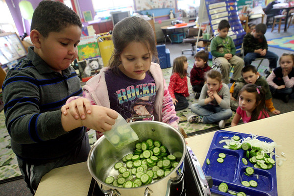 "ALLEGRA BOVERMAN/Staff photo.Gloucester Daily Times. Gloucester: FoodCorps and CitySprouts hosted ""Pickle Pioneer"" day at Veterans Memorial Elementary School on Thursday. The kindergarten class taught by Janet Allen actually made pickles out of cucumbers and onions, sugar, vinegar and salt. Cameron Carroll, center, helps Elijah Barboza, left, to carefully pour cucumbers into the boiling vinegar, salt and sugar mixture."