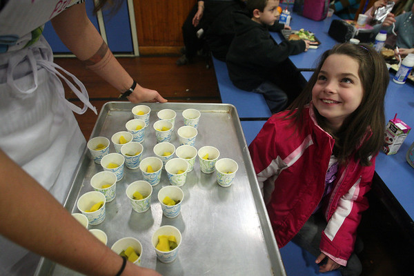 "ALLEGRA BOVERMAN/Staff photo.Gloucester Daily Times. Gloucester: FoodCorps and CitySprouts hosted ""Pickle Pioneer"" day at Veterans Memorial Elementary School on Thursday. They served different kinds of pickles at lunch and kids had to vote on their favorites among daikon radishes and cucumbers. Grace Cherubino, left, a FoodCorps service member, offers samples to second grader Hailey Gadbois."