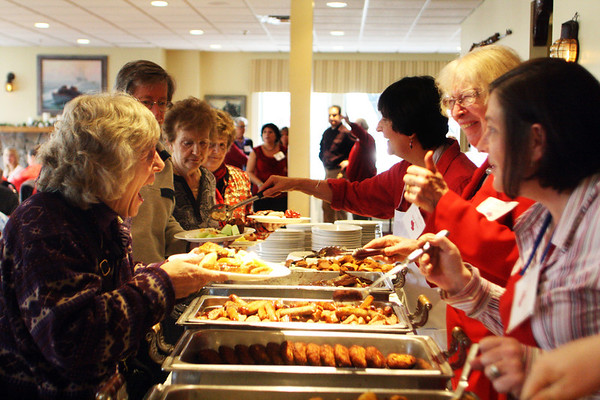 From right, Annemarie Beauparlant, Bea Robbins and Sarah Wetzel, all of Seniorcare, serve a line people awaiting their Meals on Wheels Valentine's Day Fund-raiser breakfast at the Gloucester House on Tuesday morning. Robbins jokes with Trish Roach of Gloucester. Jesse Poole/Gloucester Daily Times Feb. 14, 2012