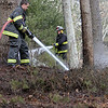 ALLEGRA BOVERMAN/Staff photo. Essex: Essex firefighters put out three separate brush fires that grew from controlled burns at 32 Haskell Court in Essex on Tuesday. Firefighters David Barrett, left, and Edward Neal, upper right, spray water to saturate the area.