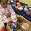 ALLEGRA BOVERMAN/Staff photo. Gloucester Daily Times. Gloucester: Bezzie Strong, 6, of Gloucester, carefully packs finished painted bowls for transport to the kiln of Marty Morgan in Gloucester.