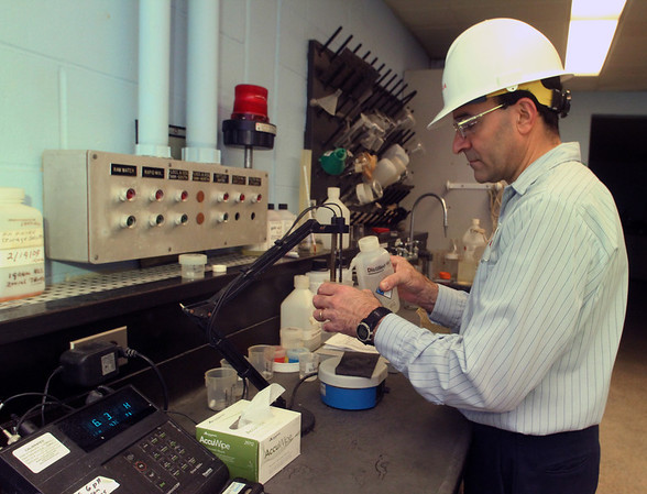 ALLEGRA BOVERMAN/Staff photo.Gloucester Daily Times. Gloucester: George Glaros, an operator of the Bond Hill Water Facility of the water division of the Department of Public Works, checks the pH level of a sample of water on Thursday in the lab.