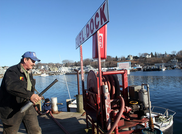 ALLEGRA BOVERMAN/Staff photo. Gloucester Daily Times. Gloucester: Ed Wayman, foreman of Gloucester Marine Railways, puts away his hose after refueling a fishing boat on Thursday.