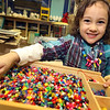 ALLEGRA BOVERMAN/Staff photo. Gloucester Daily Times. Gloucester: Ella Maria Zarcone, 3, of Gloucester, made a bracelet and necklace during the jewelrymaking session at Art Haven on Friday.