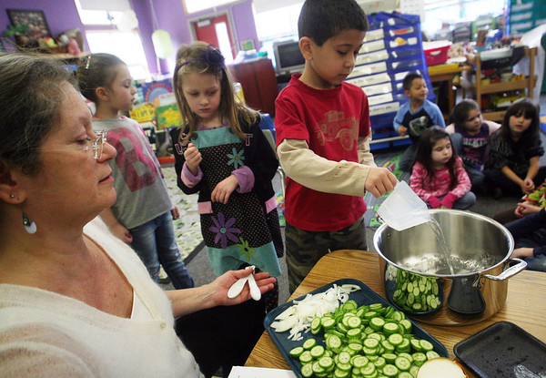 "ALLEGRA BOVERMAN/Staff photo.Gloucester Daily Times. Gloucester: FoodCorps and CitySprouts hosted ""Pickle Pioneer"" day at Veterans Memorial Elementary School on Thursday. The kindergarten class taught by Janet Allen, at far left, actually made pickles out of cucumbers and onions, sugar, vinegar and salt. Pouring ingredients in at center is Ryan DeSouza, and Kylah Plante and Aubrey Girard-Bertolino wait their turns to help."