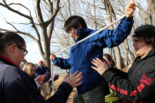 "ALLEGRA BOVERMAN/Staff photo. Gloucester Daily Times. Gloucester: In a ""tension traverse"" exercise, Tetsu Takano, center, tries to carefully make his way on a low hanging rope as others stand ready to catch him if he were to fall. At far right is Dylan Spellman, at far right is Kayla Collibee, and second from left is Jacklyn Canillas. Project Adventure of Gloucester High School and Project Adventure of Japan convened at the high school on Wednesday for activities."