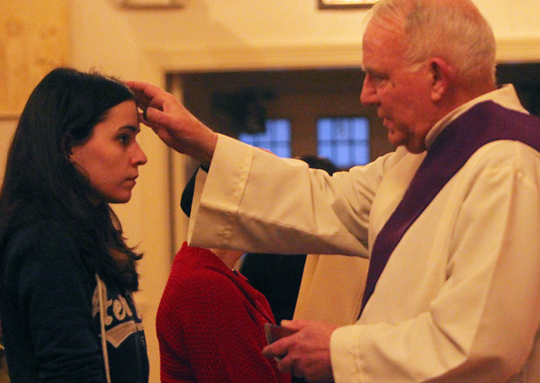 ALLEGRA BOVERMAN/Staff photo. Gloucester Daily Times. Rockport: Deacon William Kane of Saint Joachim's Catholic Church in Rockport places ashes on the forehead of Meghan McCormack of Gloucester during the Ash Wednesday service there late Wednesday afternoon.