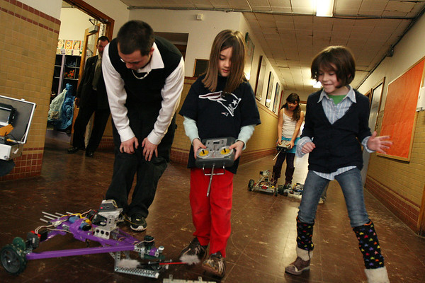 ALLEGRA BOVERMAN/Staff photo. Gloucester Daily Times. Gloucester: During a daylong visit to East Gloucester Elementary school by Gloucester High School Honors Physics and Physics of Robotics classes students on Friday. From left: GHS senior David Smith works with second graders Annie Kate Convey, center, and Lily Muniz, to operate his triangular robot he built with classmate Sean Dunne (not shown). The robot has a helicopter blade on the front and a video camera on top, and was built with creativity and innovative design in mind. In the background is second grader Lidia Quintanilha, operating a robot.
