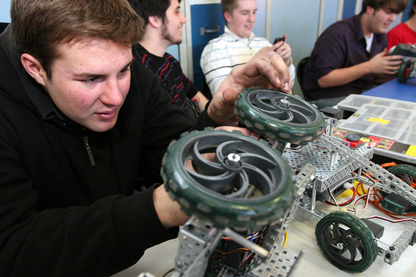 ALLEGRA BOVERMAN/Staff photo. Gloucester Daily Times. Gloucester: During a daylong visit to East Gloucester Elementary school by Gloucester High School Honors Physics and Physics of Robotics classes students on Friday. Junior Dustin McComiskey makes some repairs to a robot that was used a little too much on Friday by students.