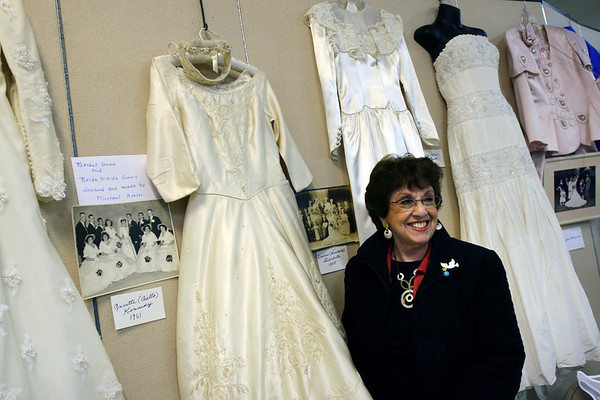 "ALLEGRA BOVERMAN/Staff photo. Gloucester Daily Times. Gloucester: The Women's Guild of Holy Family Parish held a ""Romance""- themed evening on Tuesday night at St. Ann Church. Members brought three generations of wedding dresses to display, wedding photos and wedding album, cake toppers, bridesmaid and mother-of-the-bride dresses and other memorabilia. There was a candy table, cupcakes on every table, and champagne, too. Annette Aiello Kennedy, who was married in 1961, with her wedding dress designed by her older brother, Michael Aiello of Gloucester, a longtime designer at Priscilla of Boston. He was very early into his design career when he created her dress, she said."