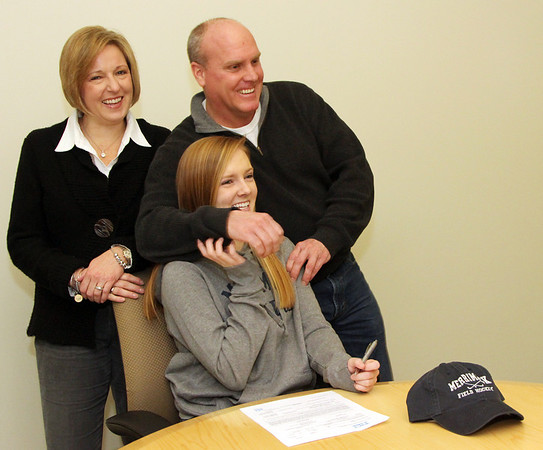 Allegra Boverman/Gloucester Daily Times. Nicole Bradley, a senior field hockey player at Manchester Essex Regional High School, center, signed a letter of intent on Wednesday to attend Merrimack College and play field hockey there. Around her are her parents, Karen and Rob Bradley.