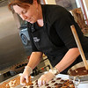 Allegra Boverman/Gloucester Daily Times. Turtle Alley Chocolates owner Hallie Baker whips up a new batch of turtles at the store on Wednesday.