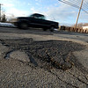 Jim Vaiknoras/Gloucester Daily Times: A car drives by a pothole on Washington Street near Colburn Ave in Gloucester Wednesday.