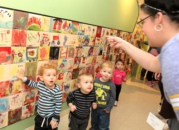 Allegra Boverman/Gloucester Daily Times.  Children in the Pathways for Children Infant and Toddler program look for thier tiles on the new mosaic wall installed recently at the center. All children at the center decorated a tile in 2012 for this wall. From left are: Jayden Conrad, 2, Owen Roberts, 2, Evan Rogers, 2, and Lily-Lee Milner, 18 months old. With them is Breianne Martell, far right.