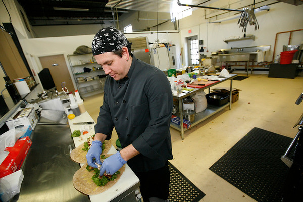 Allegra Boverman/Gloucester Daily Times. Wally's Blackburn Bistro has just opened in Blackburn Center. Paul Franklin and his wife Danika Franklin co-own the eatery. He is preparing a chicken club wrap on Monday.