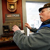 Allegra Boverman/Gloucester Daily Times. Gaybrook Garage in Essex is changing hands. Stan Collinson demonstrates how the shop's antique cash register works. Mike Crowley, one of their employees, will now run the garage.