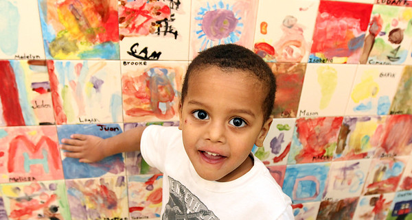 Allegra Boverman/Gloucester Daily Times.  Juan Rodriguez, 3, touches the tile he painted for the Pathways for Children mosaic recently installed at the Gloucester center. In 2012, all the children painted tiles that were installed in a path-shaped mosaic with the help of Rockport artist Eileen Mueller.