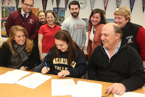 Allegra Boverman/Gloucester Daily Times. Bianca Giacalone, a Gloucester High School senior, seated at center, signed a letter of intent on Wednesday to attend Merrimack College and play soccer and run track and field there. Seated around her are her parents, Melissa Tarr and Paul Giacalone. Behind her from far left are: Dean of Students Christopher Kobs,  Assistant girls soccer coach Ali Walsh, girls head soccer coach Alex White, Jeff Destino, track and field coach, Liz Moran, track and field coach, and athletic director Kim Patience. Also in the photo but hidden is Principal Erik Anderson.