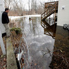 Allegra Boverman/Gloucester Daily Times. John Harvey of J.M. Harvey Glass, looks at the flooding behind the family business and their neighbors along Maplewood Avenue and Myrtle Square.