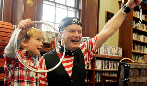 Allegra Boverman/Gloucester Daily Times. Magician Robb Preskins, right, performs a magic trick with the help of Bailey Roy, 4, during the Magic Pirate Show held at Manchester Public Library on Tuesday.
