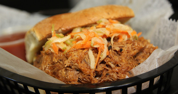 Allegra Boverman/Gloucester Daily Times. Wally's Blackburn Bistro has just opened in Blackburn Center. Paul Franklin and his wife Danika Franklin co-own the eatery. Paul prepared a pulled pork sandwich on Monday.