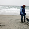 Allegra Boverman/Gloucester Daily Times. Michelle Fowler of Gloucester walks along Long Beach, her favorite beach, with her dog Penny on Friday morning at high tide and the snowstorm was beginning.