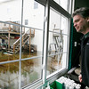 Allegra Boverman/Gloucester Daily Times. John Harvey of J.M. Harvey Glass looks at the flooding behind the family business and their neighbors along Maplewood Avenue and Myrtle Square.