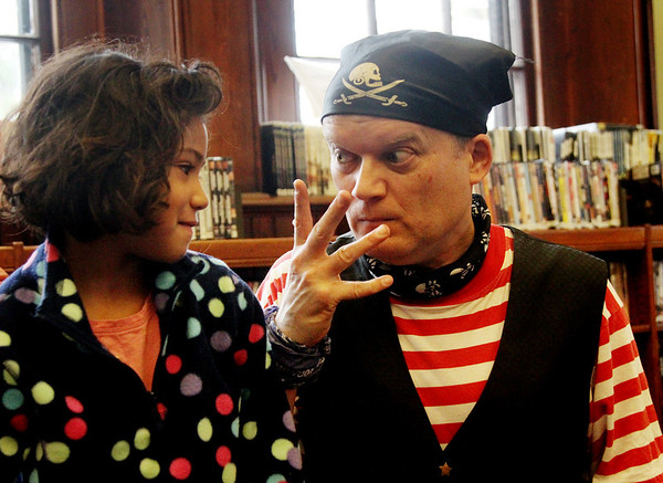 Allegra Boverman/Gloucester Daily Times. Magician Robb Preskins teases Kianna Sholds, 7, left, as she assisted him during his magic show held at Manchester Public Library on Tuesday.