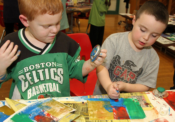Allegra Boverman/Gloucester Daily Times. Kaiden McKeney, left, a kindergartener at Essex Elementary School, and his cousin Charlie Hultgren, a first grader from Lynn, work together at the monoprint table presented by Helen Tory, a printmaker from Essex and of the Essex Art Center in Lawrence, during the fourth annual Messy Art Night at the school on Friday evening. The Essex Elementary School PTO sponsored the event, which featured over a dozen local artists plus the staffs of Art Haven, Cogswell Grant and the Essex Shipbuilding Museum.