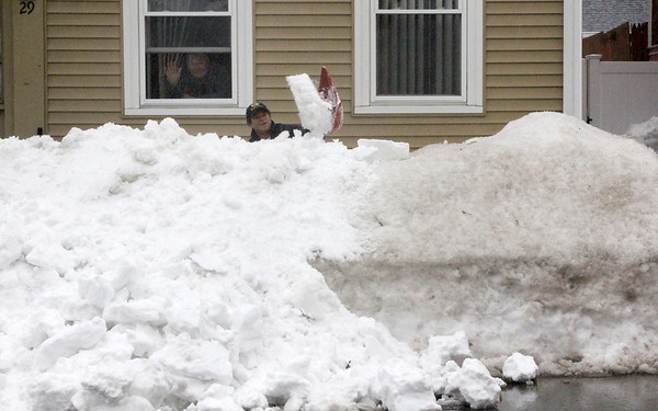 Allegra Boverman/Gloucester Daily Times. Gerald Rose was working hard on Monday afternoon digging out the sidewalk in front of the home he also shares with his sister and brother-in-law (waving at the window) Paul Lankiewicz.