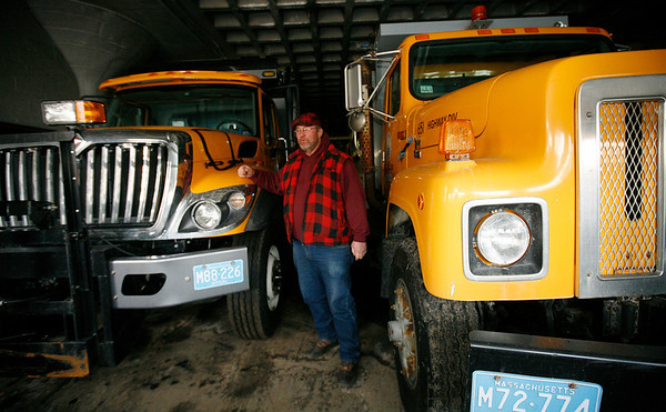 Allegra Boverman/Gloucester Daily Times. Peter Dennen, supervisor of highway and public properties, talks about how the Department of Public Works is preparing for the storm this weekend. He is standing next to the newest truck in the fleet, left, and the largest, right, that will be working in the storm to plow and salt roads.
