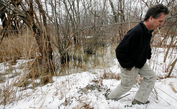 Allegra Boverman/Gloucester Daily Times. John Harvey of J.M. Harvey Glass looks at the flooding behind the family business along Maplewood Avenue and Myrtle Square.