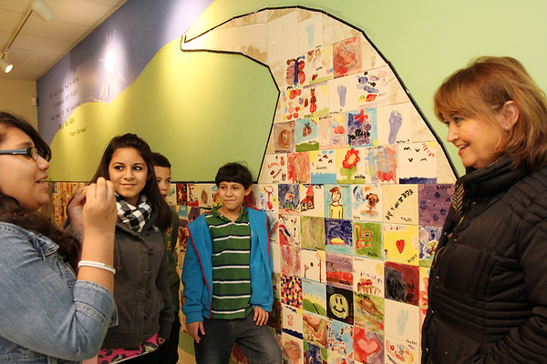 Allegra Boverman/Gloucester Daily Times.  Rockport artist Eileen Mueller, right, talks with some of the students who attend Pathways for Children near the mosaic wall she worked with them to create. It was installed recently. All the program's children painted a tile for the piece. From left, talking about their tiles are: Elizabeth Arias, 12, Juleika Rodriguez,  12, Shayne Unis, 11, and Jose Rodriguez, 12.
