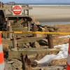"""Allegra Boverman/Gloucester Daily Times. The Gloucester Department of Public Works demolished the most damaged part of the footbridge at Good Harbor Beach on Friday morning, putting up barriers, caution tape and a """"do not enter"""" sign."""