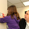 Allegra Boverman/Gloucester Daily Times. Grace Campanello, 10, daughter of Gloucester Police Chief Leonard Campanello, right, hangs up a new sign in the police station that states the police department's mission statement. She and her sister Faith, 8, were at the station with their dad while on school vacation on Thursday. New signs are being hung, new nameplates for offices being installed and general sprucing up of the station are taking place at the moment.