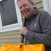 Allegra Boverman/Gloucester Daily Times. Paul Lankiewicz of Washington Street cheerfully holds one of a few shovels he owns that have a particular message written on them.