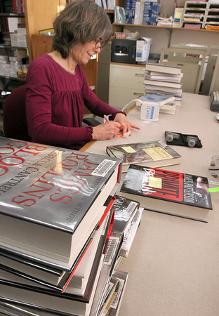 Allegra Boverman/Gloucester Daily Times. Mary Dakin, a library assistant at Rockport Public Library, prepares new books for shelving on Monday. She was affixing various labels, stamping the library's name inside and on the top, attaching the date due slip and taping the bar code into place.