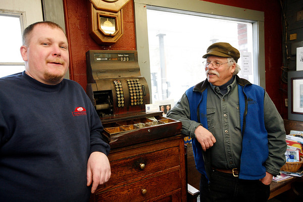 Allegra Boverman/Gloucester Daily Times. Gaybrook Garage in Essex is changing hands. Stan Collinson, right, and his wife Daisy Nell have sold the historic garage to their employee Mike Crowley, left. They are with the antique cash register that still works in the shop.
