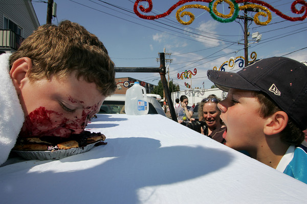 Gloucester: Nick Cassettari, 9, eats his blueberry pie as fast as he can with his older brother Chris, 11, cheering him on during the pie eating contest at Beach Court Saturday aftertoon. Nick finished in first place as did Chris when it was his turn to compete. Mary Muckenhoupt/Gloucester Daily Times