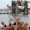 Gloucester: Jason Favaloro is carried onto Pavilion Beach after capturing the flag at the end of the greasy pole Friday.  Mary Muckebhoupt/Gloucester Daily Times