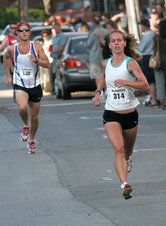Gloucester: Christa Plummer of Quakertown, PA was the first female to cross the finish line of the Fiesta 5K Road Race yesterday evening with a time of 17:11. Matthew Curran of Gloucester, left, finished two seconds behind her. Photo by Kate Glass/Gloucester Daily Times Thursday, June 25, 2009