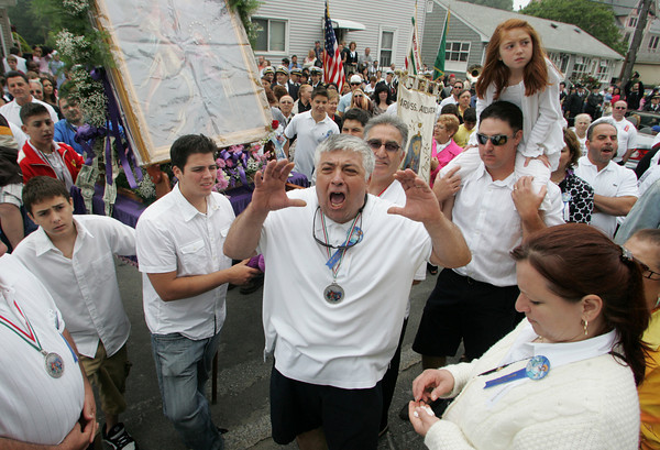 Gloucester: Vito Ferrara standing in front of the shrine carried for Maria Annunziata praises St. Peter in front of St. Ann church during the Fiesta procession Sunday. Photo by Mary Muckenhoupt/Gloucester Daily Times