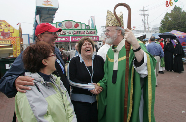 Gloucester: Cardinal Sean O'Malley greets, from left, Barbara Stanoprud, Alex Stanoprud, and Micheline McKenzie after mass at St. Peter's Square during Fiesta Sunday. Mary Muckenhoupt/Gloucester Daily Times