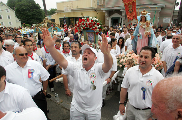 Gloucester: Gus MacIntosh praises St. Peter in front of St. Ann church during the Fiesta procession Sunday. Photo by Mary Muckenhoupt/Gloucester Daily Times