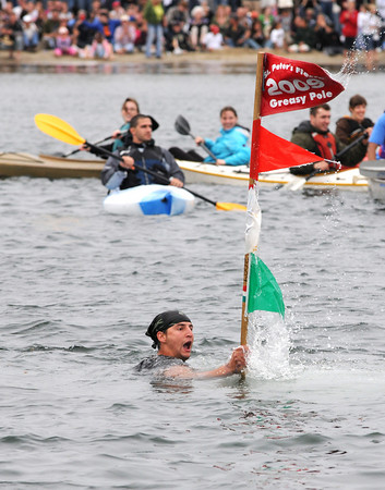 Gloucester: Stew McGillivray celebrates after grabbing the flag in the second round of the greasy pole contest Sunday afternoon. Desi Smith Photo/Gloucester Daily Times. June 28,2009