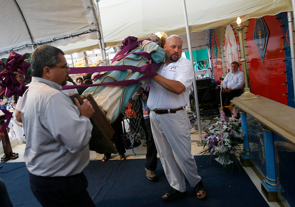 Gloucester: Warren Durgin, center, lifts the statue of St. Peter to the altar during the official opening ceremony last night. Photo by Kate Glass/Gloucester Daily Times Friday, June 26, 2009